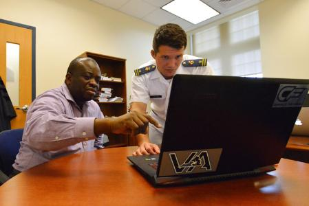 Cadet and professor look at laptop