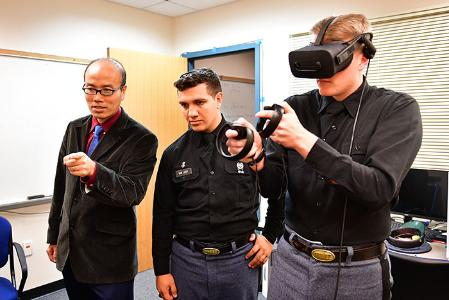 Two cadets and professor demonstrate virtual reality equipment