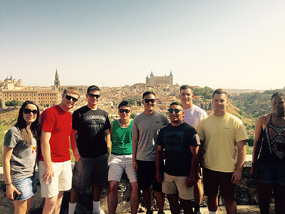 A group of cadets stand before the Toledo, Spain, skyline.