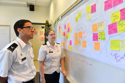Col. Troy Siemers and Maj. Jessica Libertini brainstorm ideas for the new math curriculum while looking at suggestions from other academic departments. – VMI Photo by Kelly Nye.
