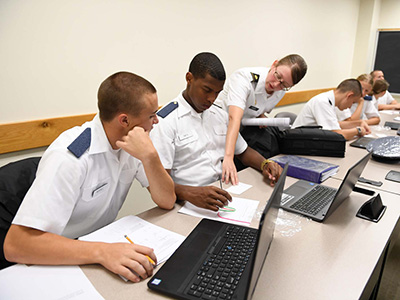 Maj. Amy Givler assists two cadets with a Wikisticks activity.