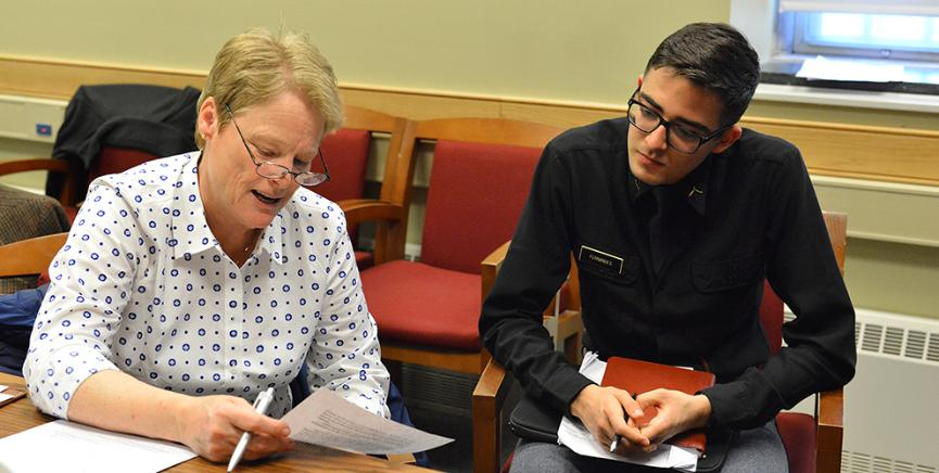 Lee Byrd reads her memoir to cadet Carlos Fernandes.
